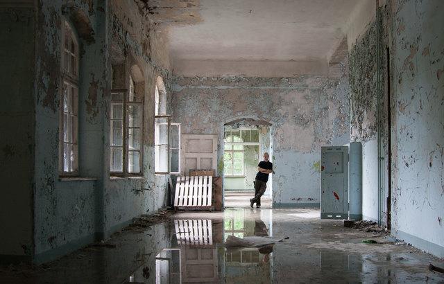 """Chris Eigner in einem verlassenen Gebäude. Der """"Urban Explorer"""" lässt zur Sicherheit sein Gesicht lieber etwas im Dunkeln."""