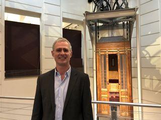 Peter Payer vor einem historischen Aufzug, der einst die Bewohner eines Mietshauses in der Kaiserstraße transportierte. Heute befindet sich der Lift im Technischen Museum.