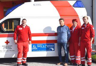 Rotkreuz-Dienstführender Franz Buchberger, Reingard Jany und die Rotkreuz-Mitarbeiterin Karin Prüller sowie Zivildiener Christian Riedl vor dem Einsatzfahrzeug.
