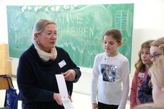 Schärdings Gym-Professorin Ingrid Thallinger mit einem Lesezeichenkalender beim Tag der offenen Tür 2017.
