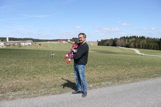 Hannes Ecker (mit seinem Enkelkind) zeigt auf das Grundstück in Oberaigen, auf dem die Nordic-Arena geplant ist.