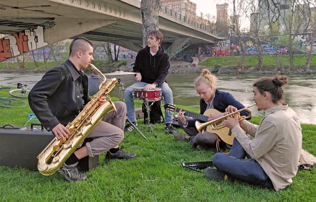 Vier der sechs Mitglieder von Buntspecht spielen am Donaukanal.