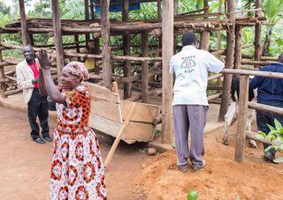 Kleinbäuerin in Uganda, die sich über die Übergabe der Milchkuh freut.