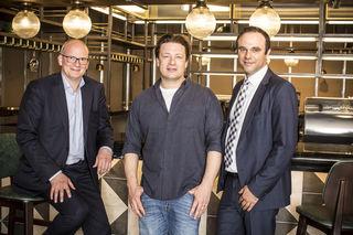 """Julian Jäger, Vorstand der Flughafen Wien AG, Starkoch Jamie Oliver, und Jan Kamp, Director Business Development SSP vor der neuen """"Jamie Oliver's Bar"""""""