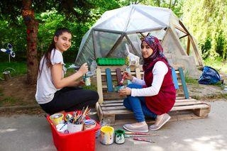 Auch das gehört zur Gartenarbeit: Eda (l.) und Ibtihal verpassen einem Palettenzaun einen hübschen, bunten Anstrich