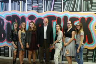 Direktor Hans Georg Gottsberger mit Schülerinnen vor der Graffiti-Wand.