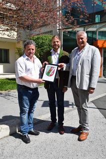 Die zwei Vizebürgermeister Franz Schlögl (l.) und Günther Bauer überreichen Patrick Helmer (m), Leiter des SeneCura Sozialzentrums Gratkorn, ein symbolisches Wappen.
