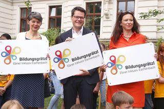 Bildungsstadtrat Jürgen Czernohorszky überreicht das Logo für das Bildungsgrätzl Ebner-Eschenbach.