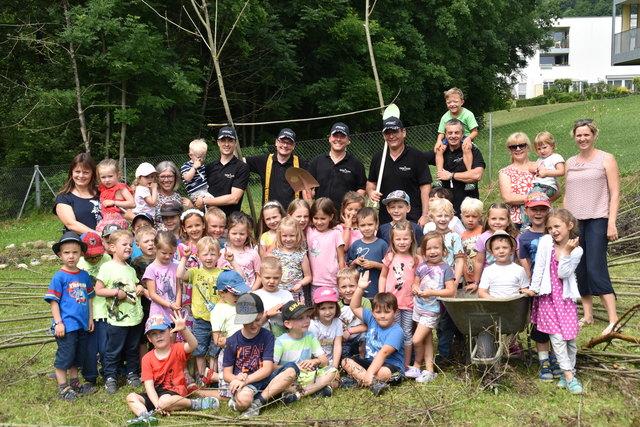 Die Casino Velden-Crew mit Kindern und Kindergartenpädagoginnen des Kindergartens Waiern beim Weidenhäuschen-Bau