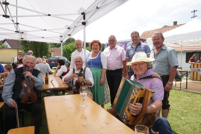 """Die Familie Reichl, Musizierende, Bgm. Rupert Fleischhacker und Vizebgm. Karl Turza bei der Begrüßung auf dem """"Dorfplatzl""""."""