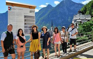 Bürgermeister Alexander Scheutz zeigt den Touristen die mehrsprachigen Willkommenstafeln in Hallstatt.