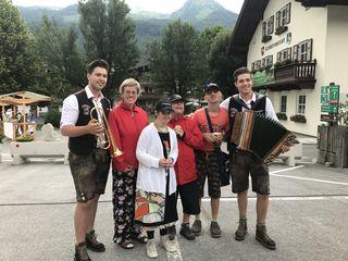 """Gut gelaunte Klienten der Lebenshilfe - Marianne, Barbara, Günther und Josef - mit den """"Wildkogel Buam"""". Im Hintergrund rechts das Gemeindeamt."""