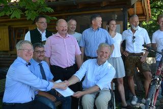 Leader-Koordinator Sebastian Wittmoser (li.) übergibt den Förderbescheid mit Handschlag an Kiefersfeldens Bgm Hajo Gruber in Beisein zahlreicher Bürgermeister udn Funktionäre.