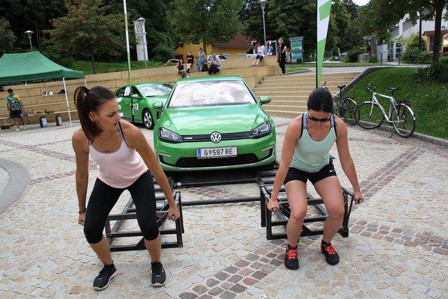 Sehr schwer, aber zu zweit geht es leichter: Carina Leitner rechts) und Michaela Liebminger beim Anheben eines Elektroautos.