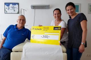 Dr. Michael Künstle mit Sybmolscheck, der von den Vorstandsmitgliedern Jasmina Auer und Martina Kappacher übergeben wurde.