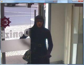 Der Bankräuber betrat die Bankfiliale mit verhülltem Gesicht und in Damenkleidern.