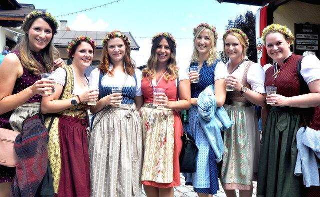Sieben blumen-geschmückte Mädchen.
