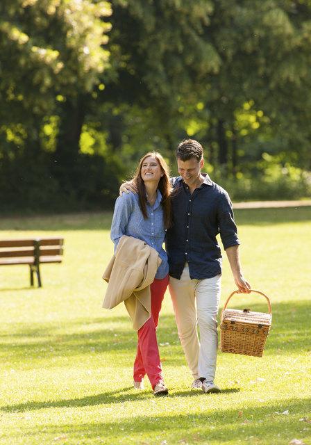 Das Paar spaziert in Park, der Picknickskorb ist bereits gefüllt.