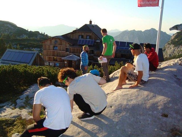 Die Teilnehmerinnen und Teilnehmer haben von der Aussichtsplattform eine gute Sicht auf das Wiesberghaus. Sie versammeln sich gerade für das traditionelle Gruppenfoto.