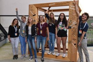 """Jugendreferentin Susanne Thaler, fünf Schülerinnen aus der """"Jugendredaktion"""" der Konferenz und der Leiter der Jugendabteilung Tobias Muster (v.l.) beim Kubus-Kunstwerk, auf dem viele Ideen der Jugendlichen festgehalten wurden."""