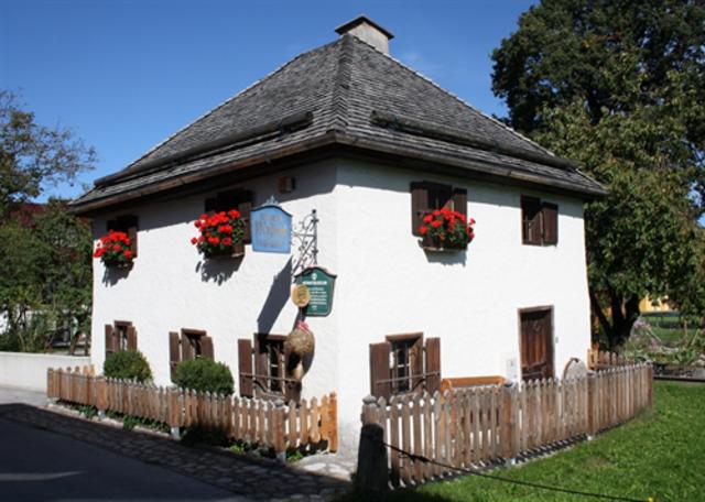 An der Außenfassade des ehemaligen Mesnerhäusls ist ein an einem geschmiedetem Träger befestigtes Schild mit der Aufschrift: 'Heimatmuseum Vigaun' zu sehen.